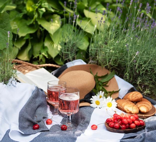 ラベンダー畑での夏のピクニック。ベリー、麦わら帽子、ワインを使った静物夏の屋外ピクニック