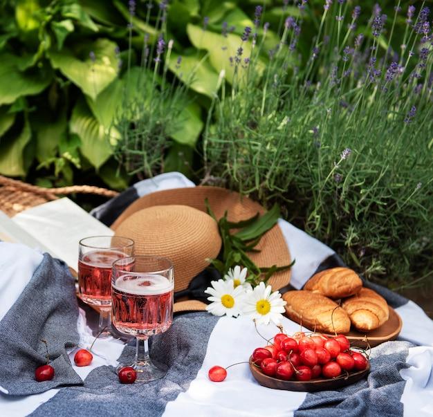라벤더 밭에서 여름 피크닉입니다. 딸기, 밀짚 모자, 와인과 함께 정물 여름 야외 피크닉