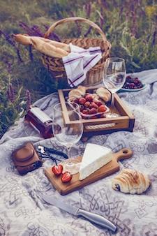 夏-牧草地でのピクニック。チーズブリーチーズ、バゲット、ストロベリー、チェリー、ワイン、クロワッサン、バスケット