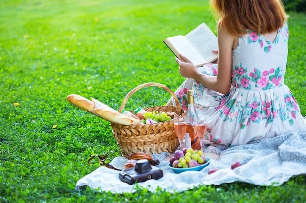 夏-牧草地でのピクニック。本を読んで、ピクニックバスケットとバゲット、ワイン、グラス、ブドウ、ロールの近くに座っている女の子