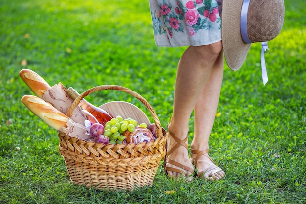 Summer - picnic on the lawn in the park.   girl and basket for a picnic with baguette, wine, glasses, grapes and rolls