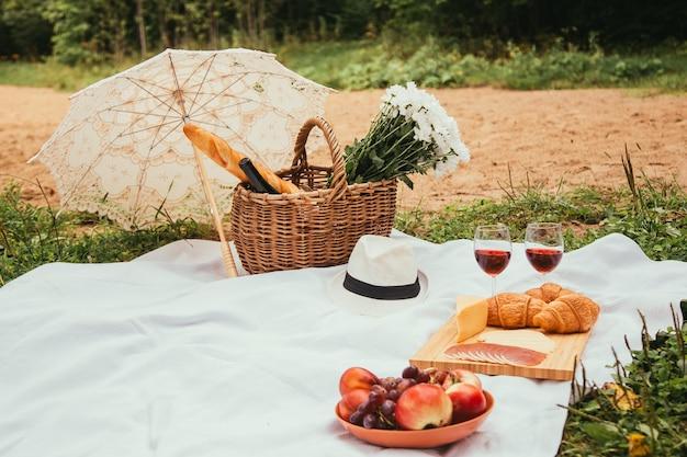 白い格子縞の食べ物や飲み物の概念で日没時のビーチで夏のピクニック