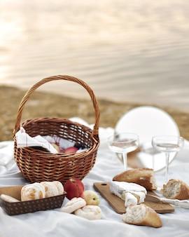夏-ビーチでのピクニック。チーズブリー、バゲット、桃、シャンパン、バスケット