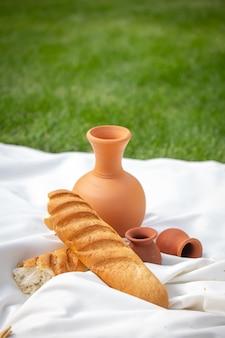 緑の芝生での夏のピクニック。粘土の水差しとパン