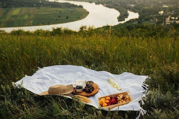 夏-絵のように美しい川と風景が表面にある丘でのピクニック。ベリー、クロワッサン、アプリコット、白ワインと緑の草の上に白い格子縞。