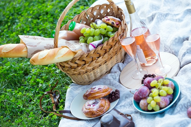 夏-公園の芝生でのピクニック。緑の芝生の上のバスケットにバゲット、ワイン、グラス、ブドウ、ロール