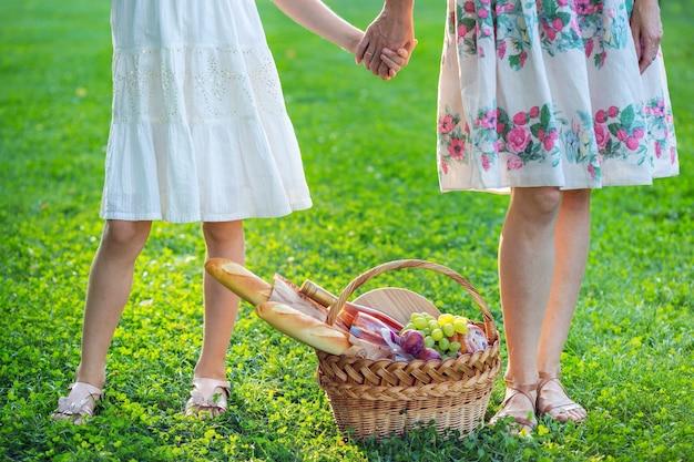 夏-公園の芝生でのピクニック。家族-バゲット、ワイン、グラス、ブドウ、ロールでピクニックのための娘とバスケットを持つ母親