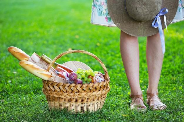 夏-公園の芝生でのピクニック。バゲット、ワイン、グラス、ブドウ、ロールパンとピクニックのための女の子とバスケット