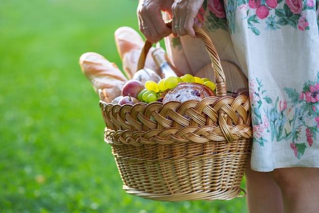 夏-公園の芝生でのピクニック。バゲット、ワイン、グラス、ブドウ、ロールパンとピクニックのバスケットを保持している女の子