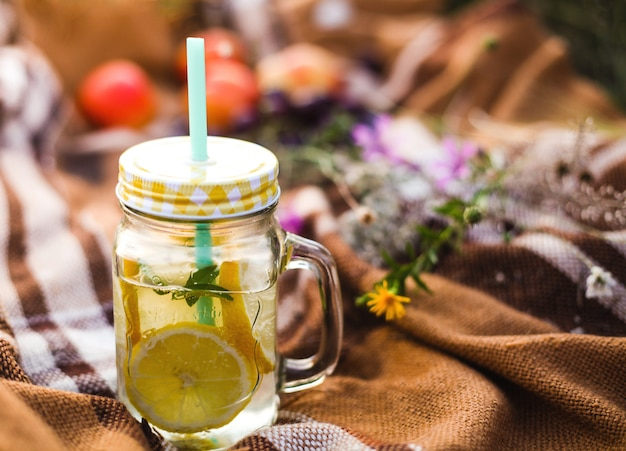 Summer picnic outdoors, summer drink jar with lemonade, plaid in the warm sunlight