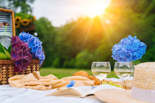 Summer picnic on sunny day with bread, fruit, bouquet hydrangea flowers