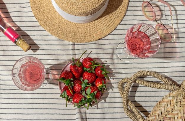 스트라이프 침대보 플랫 누워 샴페인과 딸기 여성 액세서리와 함께 여름 피크닉