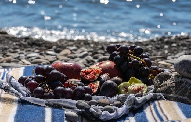Летний пикник с инжиром, виноградом и яблоками. море и плед на пляже