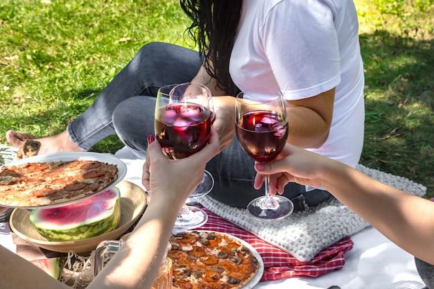 自然の中で友達と食べ物や飲み物を楽しみながら夏のピクニック。