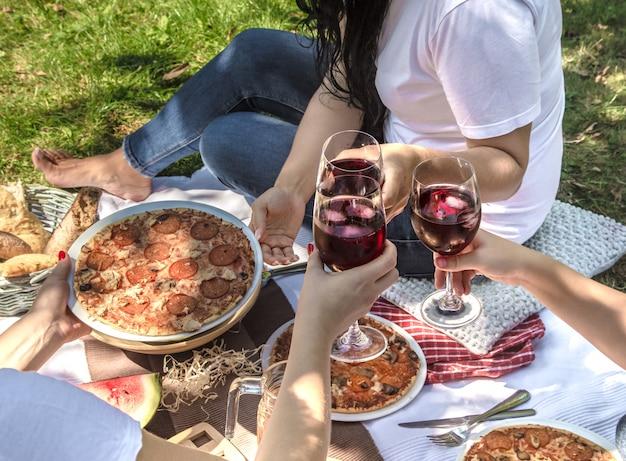 Picnic estivo con gli amici in natura con cibi e bevande.