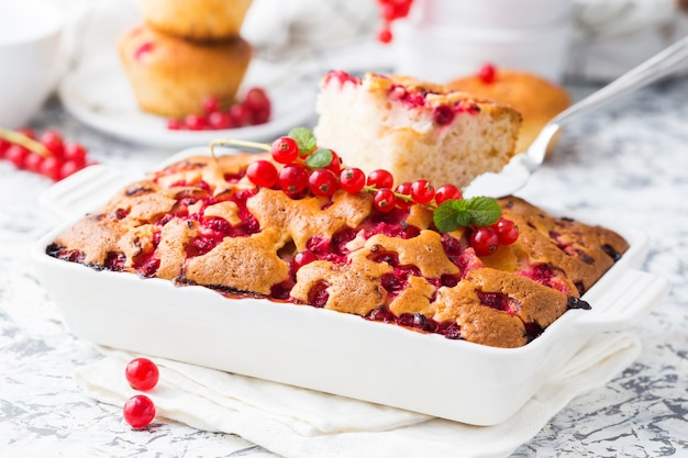 Summer pie with red currant in a white ceramic dish