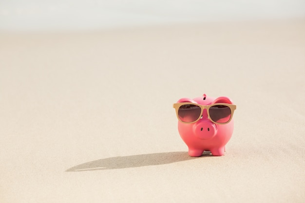 Summer piggy bank with sunglasses on sand
