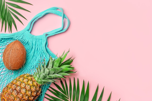 분홍색 배경에 파인애플, 코코넛, 재사용 가능한 그물 가방이 있는 여름 분홍색 배경.
