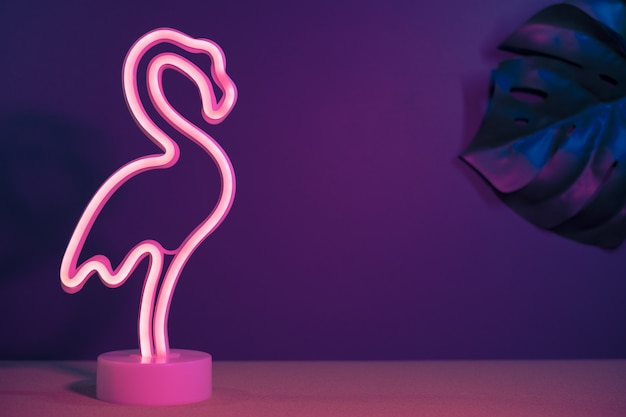 Summer pink flamingo and monstera leaf with neon pink and blue light