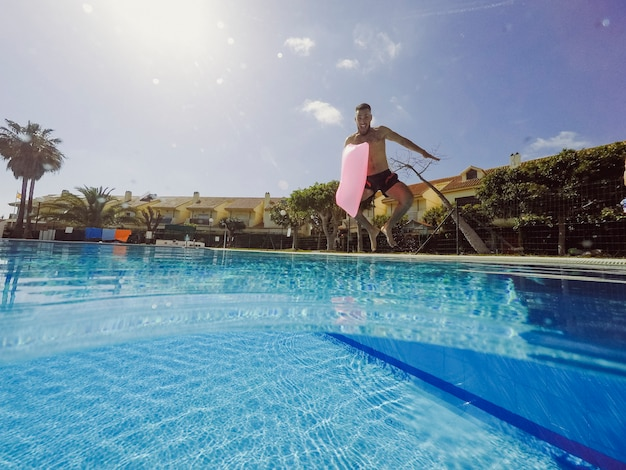 Summer and pool concept with man jumping into pool