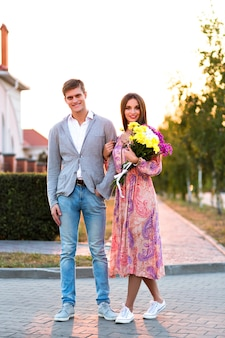 Summer portrait of amazing cute couple walking on the street, countryside sunset, elegant clothes, flowers, romantic date, cute lovers walking on the street.