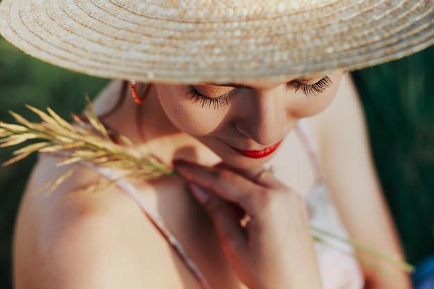 夏の肖像画、麦わら帽子を身に着けている美しいそばかすのある若い女性