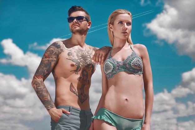 Summer portrait of fashion beautiful couple getting a suntan