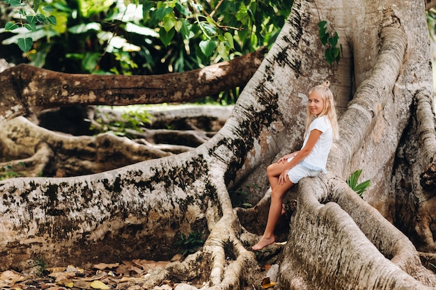 Summer portrait of a happy little girl on the island of mauritius sitting on a huge tree.a girl sits on a large tree in the botanical garden of the island of mauritius.
