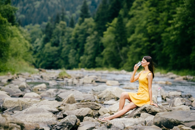 Summer portrait of lovely young brunette model in yellow dress sitting on stones in front of the river and forest and drinking water from glass.