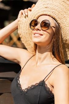 ファッショナブルな麦わら帽子とビーチで太陽の天気を楽しんでいる黒いレースのシャツのヴィンテージサングラスでかわいい笑顔で美しい幸せな女性の夏の肖像画
