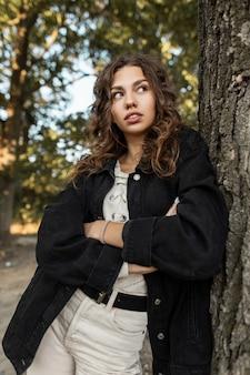 데님 블랙 재킷을 입은 아름다운 젊은 곱슬머리 여성의 여름 초상화는 자연의 나무 근처에 서 있습니다. 공원에서 시골에 청바지 옷을 입은 소녀 모델