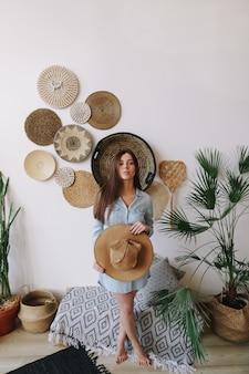 Летний портрет молодой красивой женщины в платье и шляпе в экзотическом интерьере в стиле бохо