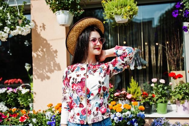 ピンクのメガネと花屋に対する帽子のブルネットの少女の夏の肖像画。