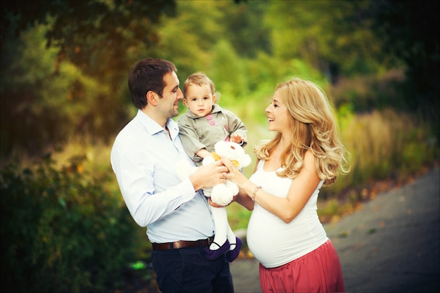 Летний портрет счастливой семьи. беременная мать, отец и маленькая дочь.