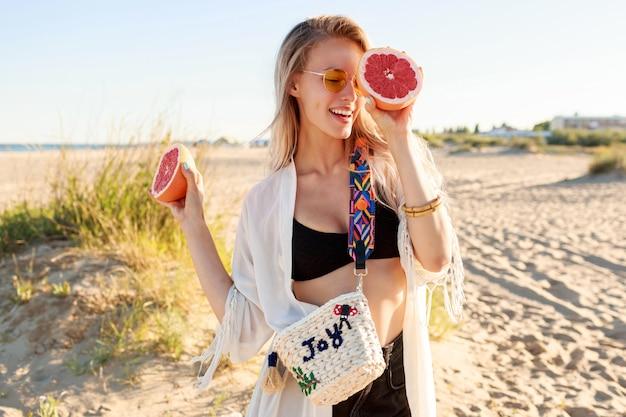 おいしいグレープフルーツの半分を手にポーズをとる遊び心のあるのんきな女性の夏の肖像画。