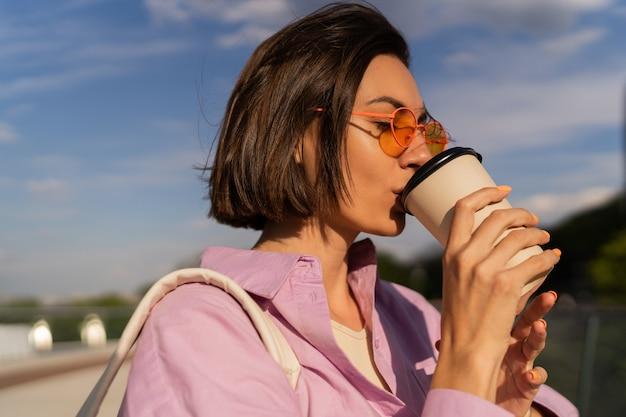 晴れた日に屋外でコーヒーを歩くスタイリッシュなサングラスでかなり短い髪の女性の夏の肖像画