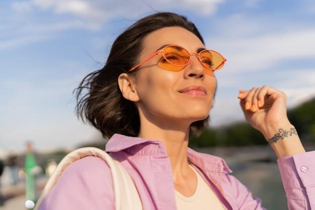 屋外を歩くスタイリッシュなサングラスでかなり短い髪の女性の夏の肖像画