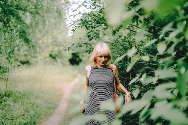 Летний портрет испуганной зрелой взрослой блондинки возле деревьев в солнечный день в парке