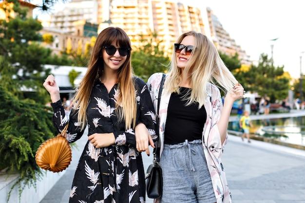 Летний портрет двух стильных красивых женщин лучших друзей, прекрасно проводящих время вместе, улыбаясь и наслаждаясь временем на улице, элегантная модная одежда просит и солнцезащитные очки, счастливая пара, отношения.