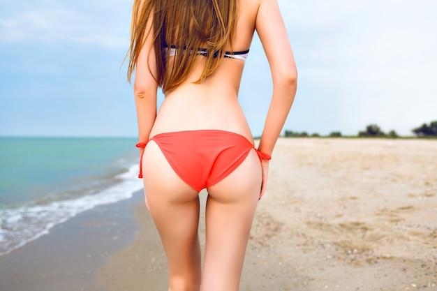 Летний портрет молодой женщины, позирующей обратно в стройное тело на пляже, пляжный отдых, в ярком бикини.