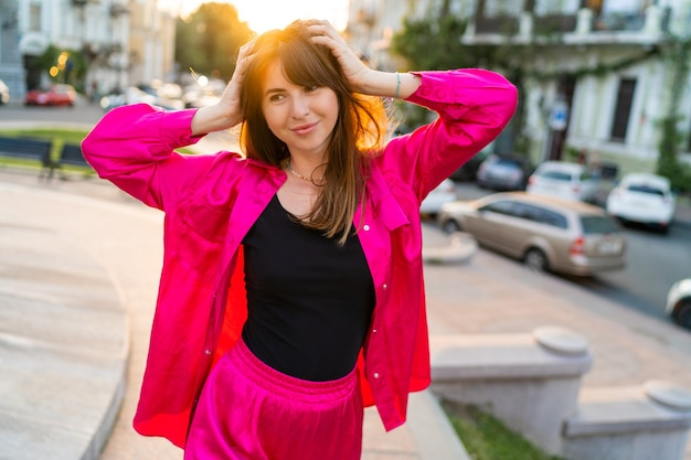 Summer portrait of playful good-looking woman in stylish pink jacket.