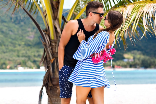 Summer portrait of pretty romantic couple having fun at tropical islands