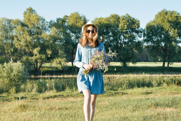 Summer portrait of teen girl with bouquet of wildflowers