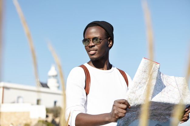 Summer portrait of young man using city guide while sightseeing in resort town