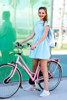 Summer positive lifestyle portrait of hipster pretty blonde woman, playful mood, riding bike on barcelonetta, pink vintage pastel style, short blue dress, silver backpack