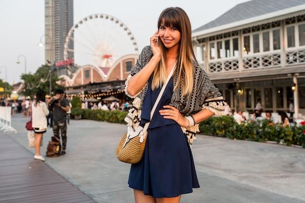 Летний позитивный портрет веселой женщины в стильном наряде, говорящей по мобильному телефону и улыбающейся на набережной в бангкоке
