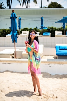 Summer positive vacation portrait of pretty brunette woman having fun at luxury beach club, slim body, trendy bikini and kimono, holding soft drink.