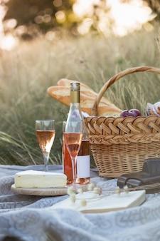 夏-牧草地でのプロヴァンスのピクニック。バゲット、ワイン、グラス、ブドウ、チーズブリーチーズ、バスケットに入ったバゲット