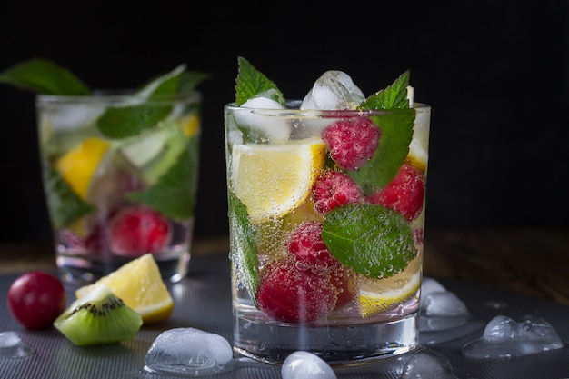 Summer refreshing carbonated drink with berries and fruits raspberry, lemon, kiwi and ice on a dark . macro