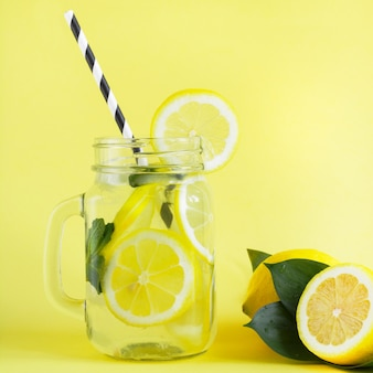 Summer refreshing cocktail with lemon, mint and ice in mason jar on yellow. tropical concept.